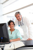 Doctor and nurse working in office — Stock Photo