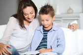Mother and son reading book on a sofa — Stock Photo