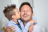 Petit garçon de liaison donnant un baiser à son papa — Photo