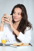 Beautiful woman having breakfast at home — Stock Photo