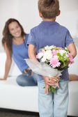 Little boy giving flowers to his mom on mother's day — Foto de Stock