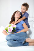 Little boy giving flowers to his mom on mother's day — Stock Photo
