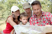Family looking at map on a hiking day — Stock Photo