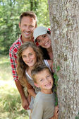 Smiling family standing behind a tree — Stock Photo