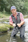 Fisherman in river with fishing rod — Stock Photo