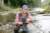 Pescatore nel fiume con la canna da pesca mosca — Foto Stock