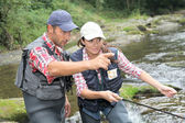 Man and woman fly fishing in river — Stockfoto