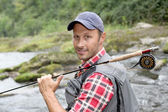 Closeup of fly-fisherman holding fishing rod in river — ストック写真