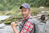 Primer plano de la barra de pesca mosca-pescador tenencia en río — Foto de Stock