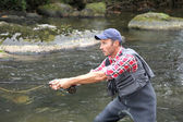 Fisherman in river with fly fishing line — Stock Photo