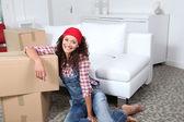 Mulher sentada no chão da sala de estar ao lado de caixas — Foto Stock