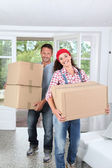 Couple holding boxes in their new home — Stock Photo