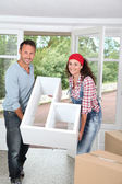 Couple holding furniture in their new home — Stock Photo