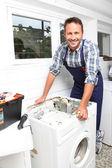Plumber fixing broken washing machine — Stock Photo