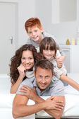 Happy family of 4 laying on a sofa at home — Stock Photo