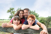 Family leaning on a fence — Stock Photo