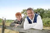 Father and son leaning on a fence — Stock Photo