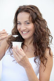 Closeup of beautiful woman eating yogurt — Stock Photo