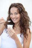 Closeup of beautiful woman eating yogurt — Stock Photo