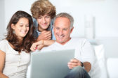 Family at home with laptop computer — Stock Photo