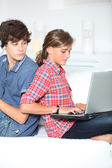 Teenagers with music player and computer at home — Stock Photo