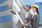 Construction engineer in front of modern building — Stock Photo