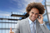 Businessman on the phone in front of modern building — Stock Photo