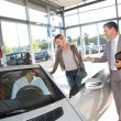 Stock Photo: Car seller with couple in car dealership