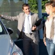 Car seller showing vehicle to couple of purchasers — Stock Photo