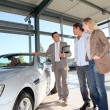 Car seller with couple in car dealership — Stock Photo #18270355