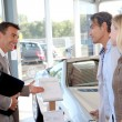 Car seller with couple in car dealership — Stock Photo #18270459