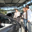 Stock Photo: Car seller with couple in showroom