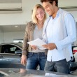 Couple reading car documentation in showroom - Stock Photo