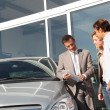 Stock Photo: Car seller with couple looking at electronic tablet