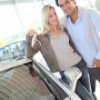 Happy couple holding new car keys — Stock Photo
