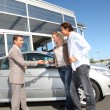 Car seller with couple outside car dealership - Stock Photo