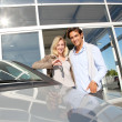 Couple holding car key in automobile dealership — Stock Photo #18270819