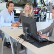 Car seller and couple of buyers signing contract — Stock Photo