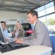 Car seller and couple of buyers signing contract - Stock Photo