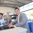 Car seller and couple of buyers signing contract — Stock Photo #18270841