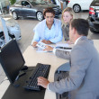 Car seller and couple looking at catalogue — Stock Photo