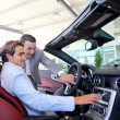 Car seller showing interior details to purchaser — Stock Photo #18270883