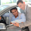 Stock Photo: Car seller with car buyer looking at electronic tablet