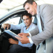 Car seller with car buyer looking at electronic tablet — 图库照片