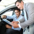 Car seller with car buyer looking at electronic tablet — Foto de Stock