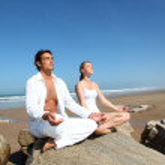 Couple doing yoga exercises on the beach — Stock Photo #18274011