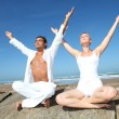Couple doing yoga exercises on the beach — Stock Photo #18274039