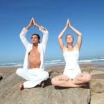 Couple doing yoga exercises on the beach — Stock Photo #18274059