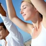 Couple doing yoga exercises on the beach — Stock Photo #18274085