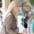 Woman standing in front of shopping windows — Stock Photo